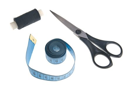 Thread on a reel, tape-line and scissors over white background photo