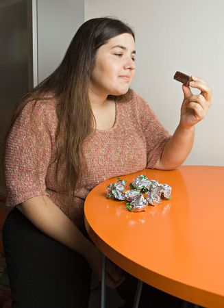 Stout woman contemplating over wrappers of sweets photo