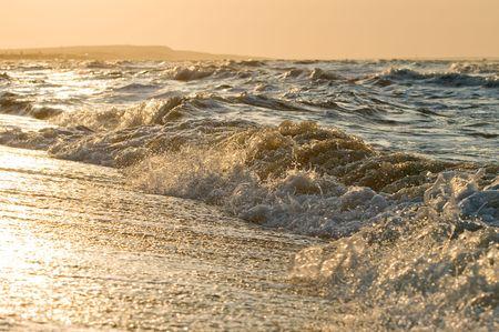 Splashing sea wave in sunset or sunrise light