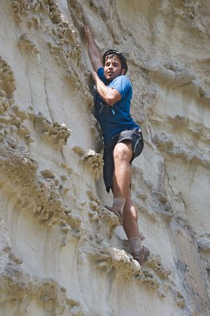 belay: Young sportsman climbing a cliff without belay