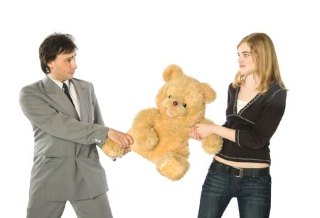 horseplay: Young man and woman fighting over a teddy-bear