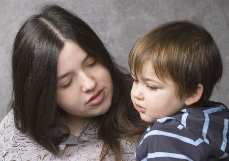 Mother consoling her son, close-up, over gray background photo