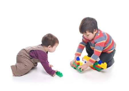 Brother and sister playing together over white background photo