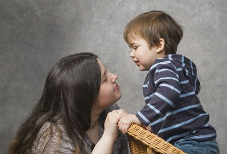 Woman speaking with her little child, studio shot photo