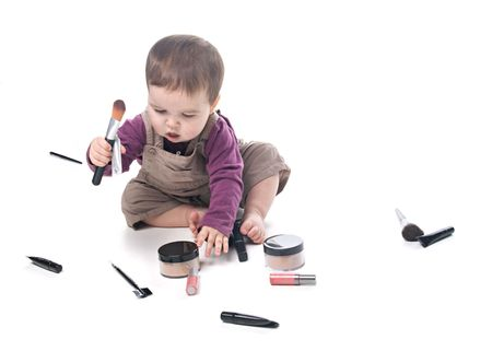 Baby girl playing with cosmetics, white background photo