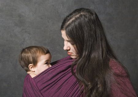 Mother with her daughter in sling, dark background photo