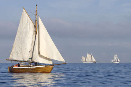 gaff: Three ships with white sails in the calm sea Stock Photo