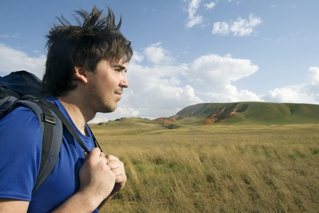 Profile of a young backpacker with green valley in the background Stock Photo - 12222603