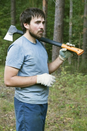 lumberman: Young lumberman in a forest with an axe on his shoulder