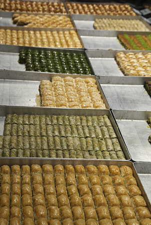 Various turkish baklava on trays in a shop photo