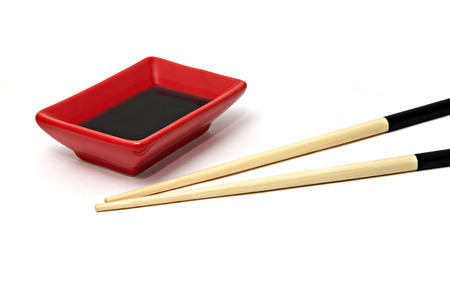 Sushi saucer and wooden chopsticks isolated over white photo