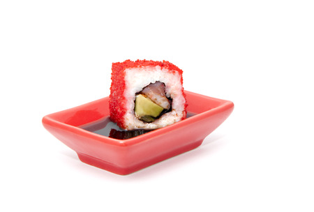 Sushi roll dipped in soy sauce, isolated over white photo