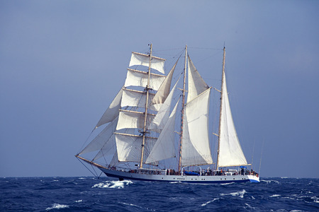 topsail: Barquentine with white sails in the calm sea