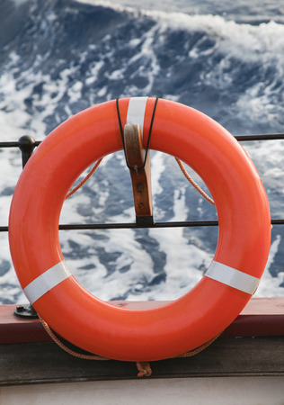 Orange lifesaver hanging on a bord of a sailing ship