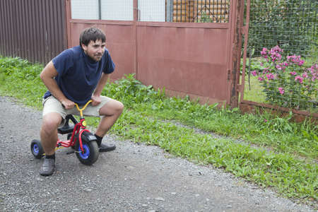 adult toys: Adult man tying to ride on a small tricycle Stock Photo