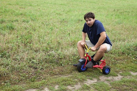 unsuitable: Adult man tying to ride on a small tricycle Stock Photo