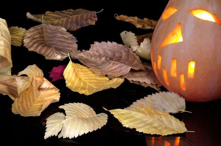 Autumn yellow leaves and pumpkin in style halloween  on a glass table photo