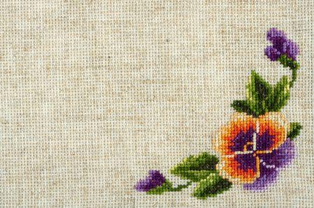 punto de cruz: Flor bordada en una muestra de un tejido