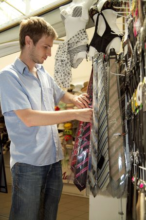 The young man chooses to itself clothes in a supermarket. photo