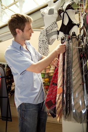 The young man chooses to itself clothes in a supermarket. Stock Photo - 5089644