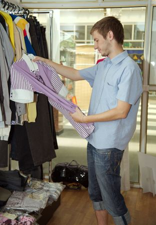 The young man chooses to itself clothes in a supermarket. Stock Photo - 5089633