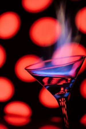 intoxicate: Blue flame of burning alcoholic drinks on a red background. Stock Photo
