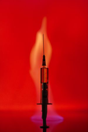 Syringe with a drug on a background of a  blue flame. photo