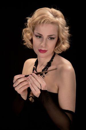 Blonde in a black dress smokes a cigarette through a mouthpiece photo