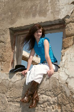 corral: Cowgirl on a background of ruins of an old farm Stock Photo