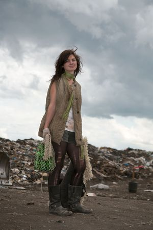 tramp: Homeless girl searches for ways of a survival on a city dump. Stock Photo