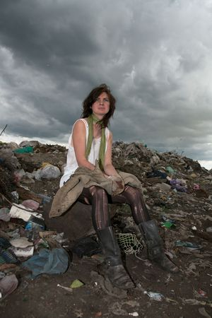 Homeless girl searches for ways of a survival on a city dump. photo