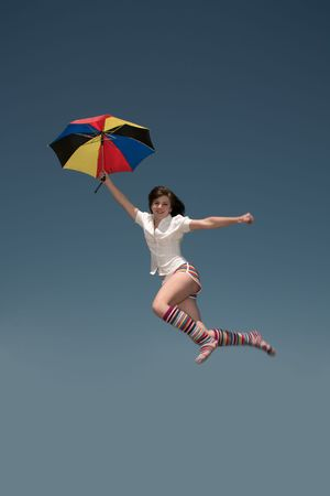 Girl with a color umbrella  jumps highly upwards. Stock Photo - 7132579