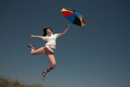 Girl with a color umbrella  jumps highly upwards. Stock Photo - 7132582