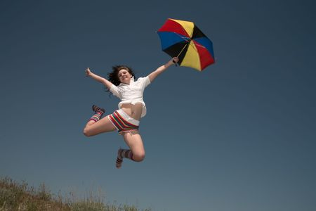 Girl with a color umbrella  jumps highly upwards. Stock Photo - 7132584