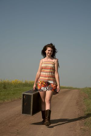 hitchhiking: Girl with the big suitcase goes on rural road Stock Photo