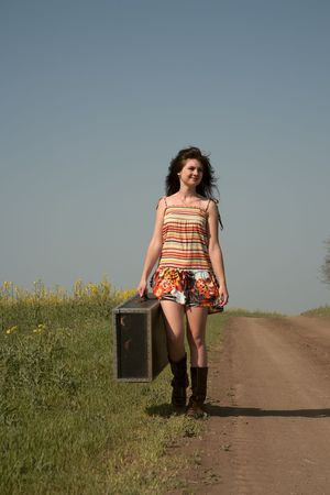 Girl with the big suitcase goes on rural road Stock Photo - 7159305