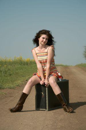 earth road: Ragazza si siede sul grande valigia. Strada di terra lungo un campo.  Archivio Fotografico