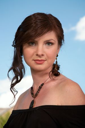 Portrait of a brunette with a classical hairdress on a background of the dark blue sky. photo