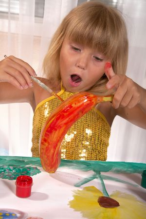 Little girl paints a banana in red color photo
