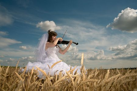 Bride in a wedding dress executes a liked composition on a violin photo