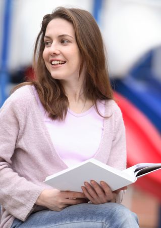 The girl sits on a bench with the book Stock Photo - 889529