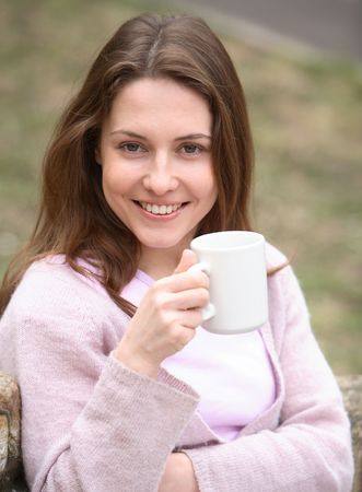 The girl holds a cup in hands and smiles Stock Photo - 894628