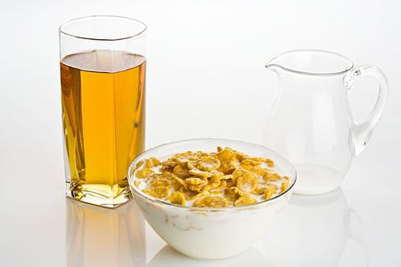 indicative: Big glass of apple juice and  corn-flakes with milk