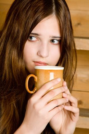 Portrait of the dark-haired girl with a mug close up  a wooden ladder background photo