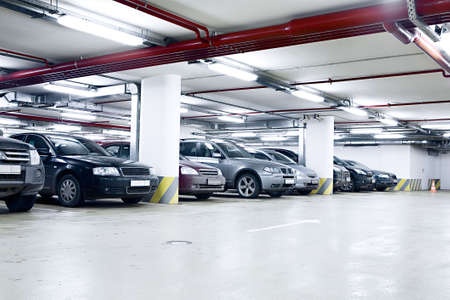 cars parking: The shined underground garage with the moving cars and parked cars