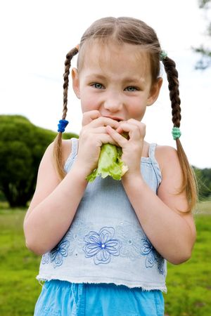 Young girl eating lettuce photo