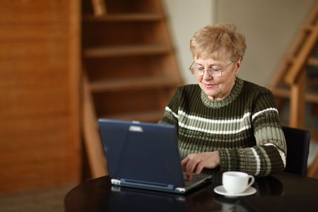 The elderly woman writes  on the computer photo