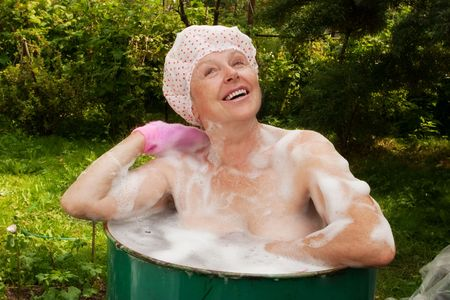 shampooing: The elderly woman washes in the cask