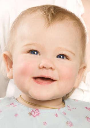 agape: The little girl in a blue dress laughsr Stock Photo