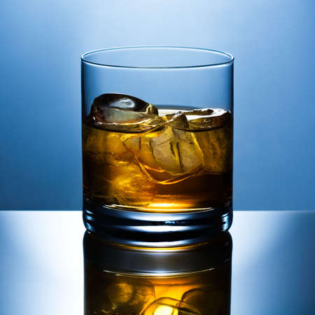 shined: Beautifully shined glass from whisky with ice is reflected in a glass table Stock Photo